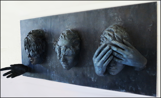 bronze relief sculpture, three faces